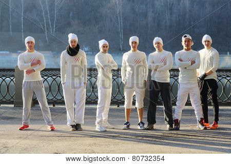 Group of seven young men in white shirts and hats stand in line on waterfront