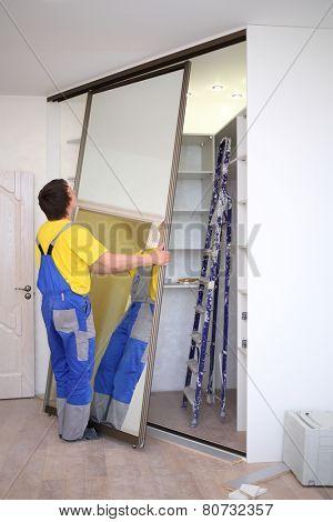 Man setting mirrored doors on corner sliding wardrobe in room