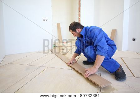 Worker in blue overalls laid wood floor in white room