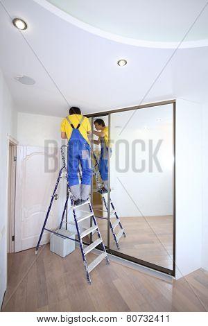 Young worker fixing mirrored door on sliding wardrobe in room