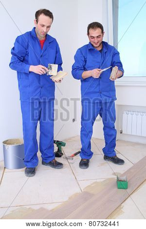 Two workers apply glue to the board for floor with a spatula in white room