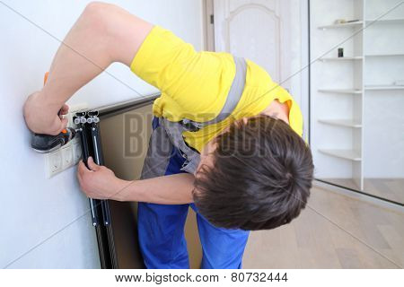 Man using perforator sets of fastening on the door for sliding wardrobe
