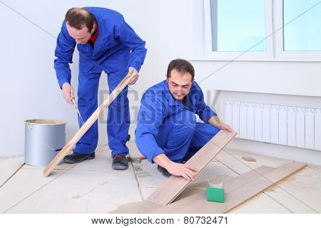 Two builders apply glue to the board with a spatula and put them on the floor