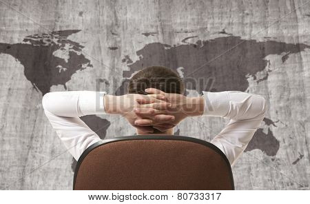 Businessman leaning back looking at world map
