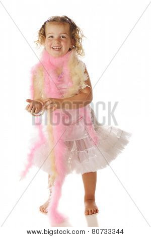 A beautiful preschool girl in boas, bracelets and a petticoat.  Isolated on white.