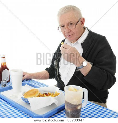 A senior adult man looking up at the viewer as he enjoys a french fry from his fast food basket.  On a white background.
