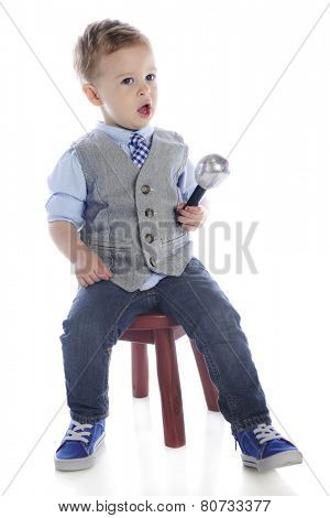Adorable preschooler singing into a mike.  On a white background.
