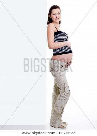 Pregnant Woman Standing Near  White Blank Banner