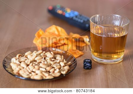 Unhealthy Snacks On Table With Skull Dice And Tv Remote