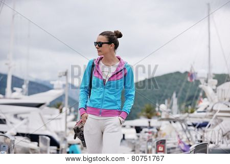 relaxed young woman walking in marina with yacht boats in bacground
