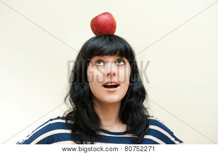 Pretty Brunette Girl Smiling And Looking Red Apple On Head
