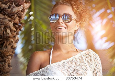 Portrait of attractive female wearing stylish sunglasses hug palm