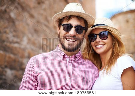 Happy girl and her boyfriend in hats and sunglasses
