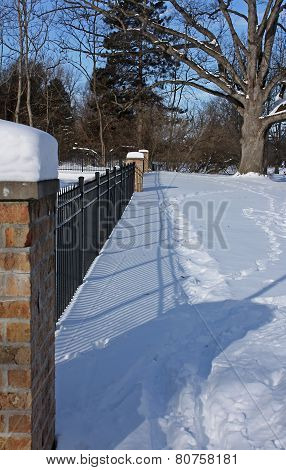 Iron Fence on a snow covered ground on a sunny winter day