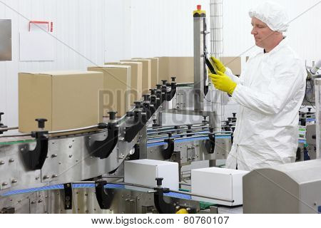 worker in apron, cap, gloves with tablet checking process at production line in factory.