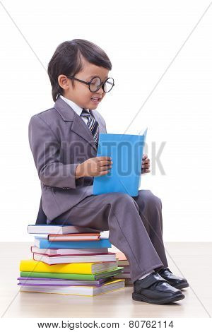 Cute boy in suit reading a book