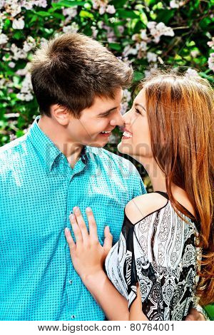 Romantic young people tenderly kissing in the summer garden. Love concept.