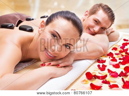 Portrait of happy smiling couple relaxing in spa salon with hot stones on body.