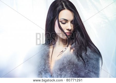 Fresh breeze is waving a hair of a beautiful young girl in fur coat
