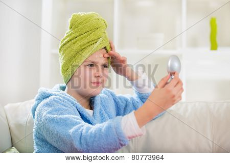 Teenager finding an acne on her forehead wit towel on her head