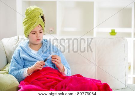 Teenager with towel on her head polishing fingernails with the nail file.
