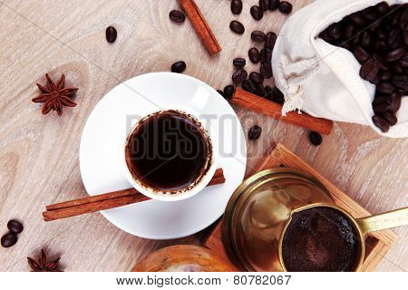 sweet hot drink : black turkish coffee in small white mug with mortar and pestle , coffee beans in white bag , copper old style cezve full hot coffee, decorated with cinnamon sticks and anise stars