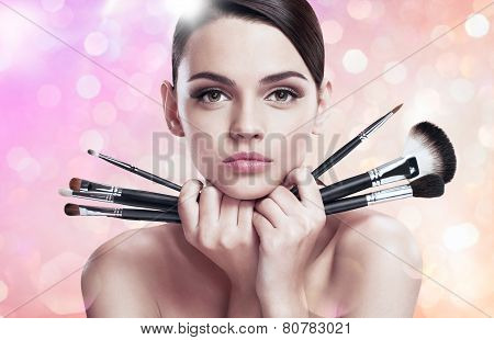 Young beautiful lady with makeup brushes near her face, skin care concept