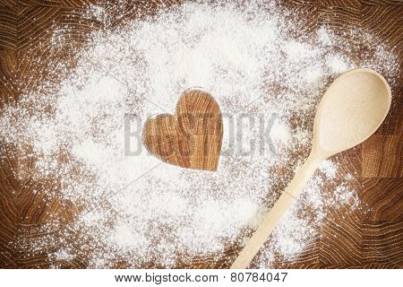 Heart of white flour on a wooden board. Cooking with love. Holiday backing background. Eco food and home cooking.
