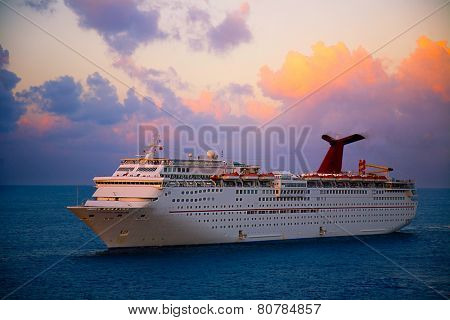 GEORGETOWN, GRAND CAYMAN - MARCH 25, 2009:  Georgetown is a popular for cruise lines in the Caribbean.  This ship is anchored off shore at sunset.