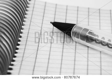 Closeup black and white image of Ball pen and office note book