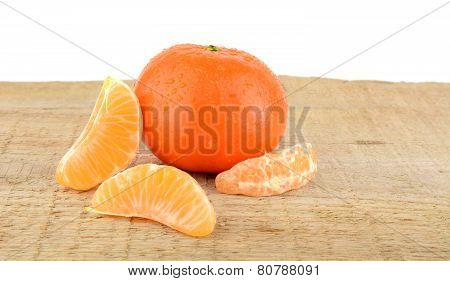 Mandarine With Pieces Isolated On Wooden Table