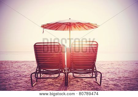 Retro Filtered Picture Of Beach Chairs And Umbrella On Sand At Sunset. Concept For Rest, Relaxation,