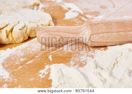 Wooden Rolling Pin And Dough On Kitchen Table