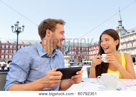 Madrid tourists at cafe drinking coffee having fun using tablet travel app on Plaza Mayor. Tourist couple sightseeing visiting tourism landmarks and attractions in Spain. Young woman and man