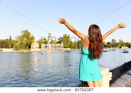 Happy success woman in Madrid park El Retiro. Successful girl cheerful with arms up outstretched in by lake Parque el Retiro in Madrid, Spain, Europe. Woman in summer dress.