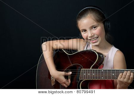A Pretty Little Girl Whit Headphones Playing Guitar