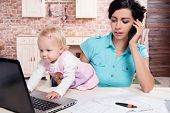 stock photo of young baby  - Young business woman working with baby in the kitchen - JPG