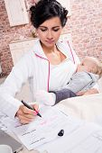 pic of young baby  - Young mother working while breastfeeding her baby - JPG