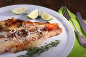 foto of pangasius  - Dish of Pangasius fillet with spices and vegetables on plate and wooden table background - JPG