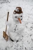 stock photo of snow shovel  - Smiling snowman standing with shovel in the snow - JPG