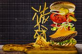 stock photo of fried onion  - Delicious french fries and cheeseburger stacked high with a juicy beef patty - JPG