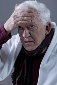 stock photo of high fever  - Pensioner having high fever touching his forehead - JPG
