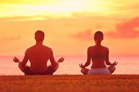 pic of beach holiday  - Meditation yoga couple meditating at serene beach sunset - JPG