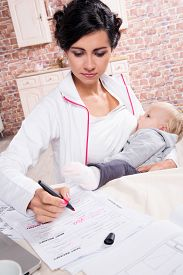 image of lactating  - Young mother working while breastfeeding her baby - JPG