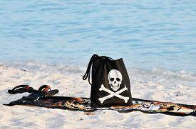 stock photo of skull crossbones  - A black beach back with a smiling skull and crossbones with a towel and flip flops  on a sandy beach - JPG