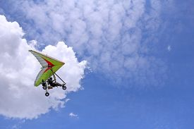picture of glider  - The motorized hang glider flying in the blue sky - JPG