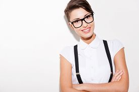foto of suspenders  - Beautiful young short hair woman in white shirt and suspenders keeping arms crossed and smiling - JPG