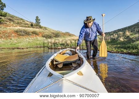 senior paddler and decked expedition canoe on the shore of Horsetooth Reservoir, Fort Collins, Colorado, springtime scenery