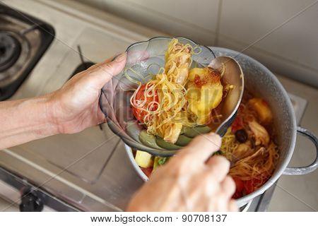 Hand serving chicken stew in a bowl