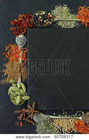 different spices on a black background (paprika, turmeric, pepper, aniseed, cinnamon, saffron)